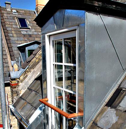 Kvist på byggeforeningshus inddækket i zink i forbindelse med etablering af en fransk altan. Da der blev skåret op i murkronen,  blev denne ligeledes inddækket i zink.